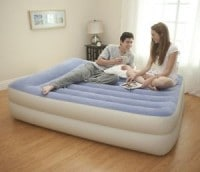 A couple sitting on an air mattress