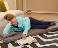 A woman laying on a floor mattress