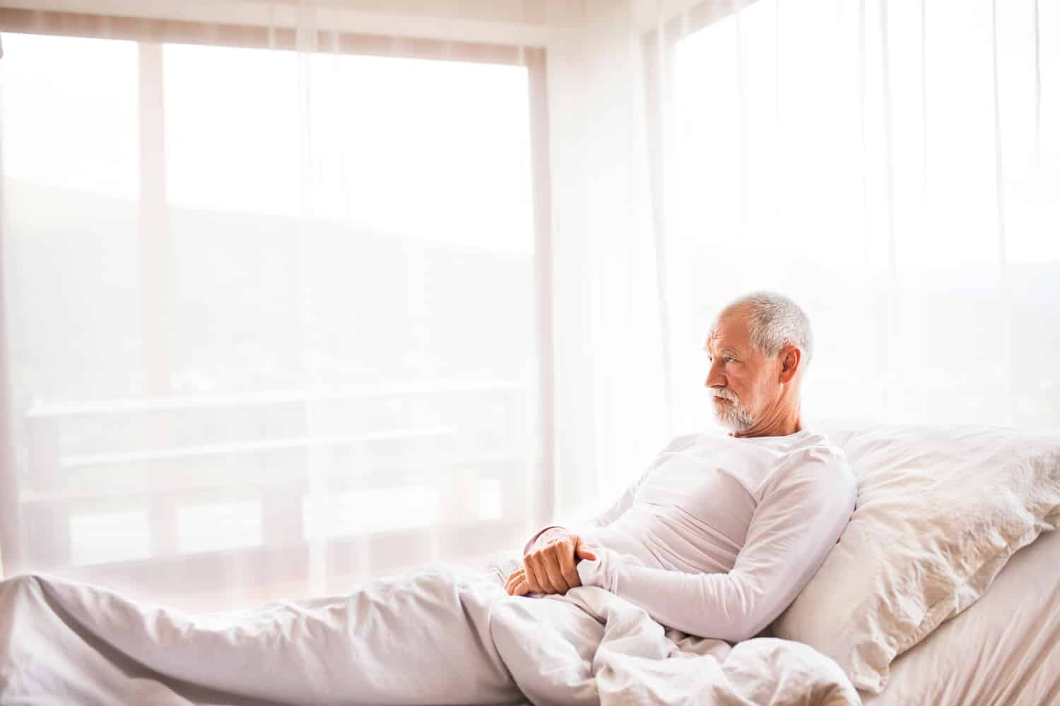 Senior man lying in adjustable bed at home.