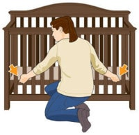 Woman adjusting the baby crib height