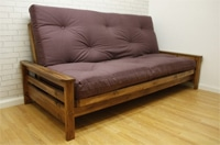A bi fold futon mattress on a wooden frame