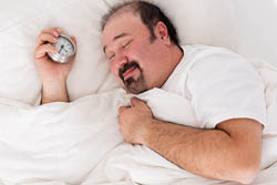 A heavy man sleeping and smiling