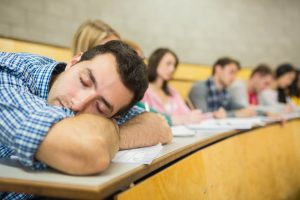 A student falls asleep at his desk in class