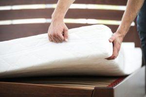 A man lifting a mattress