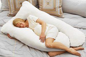 Woman using a total body pregnancy pillow
