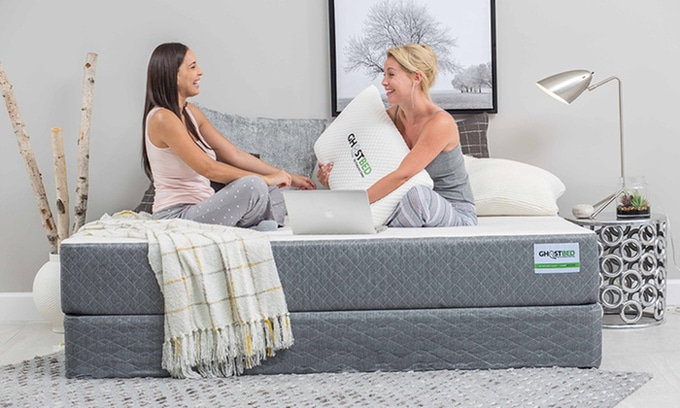 Two ladies sitting on a new Ghostbed mattress and boxspring