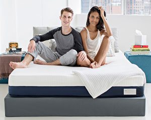 A young couple sat on their bed