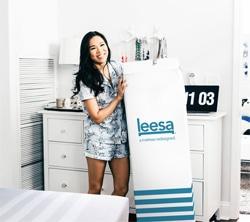 Girl holding a Leesa Mattress in a box