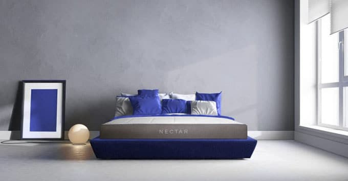 A Nectar mattress on a purple colored bed