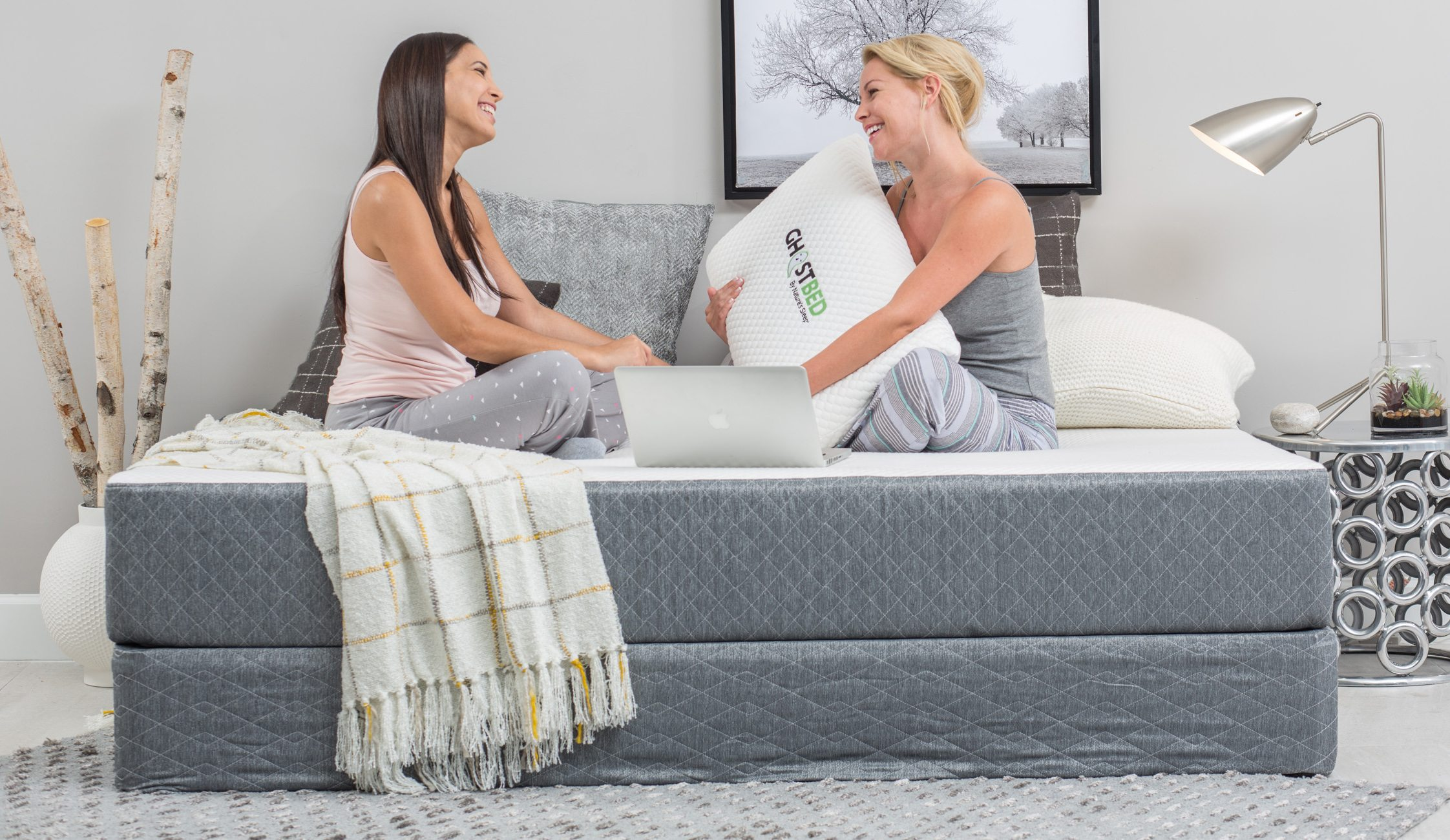 Two women sitting and talking on a Ghostbed