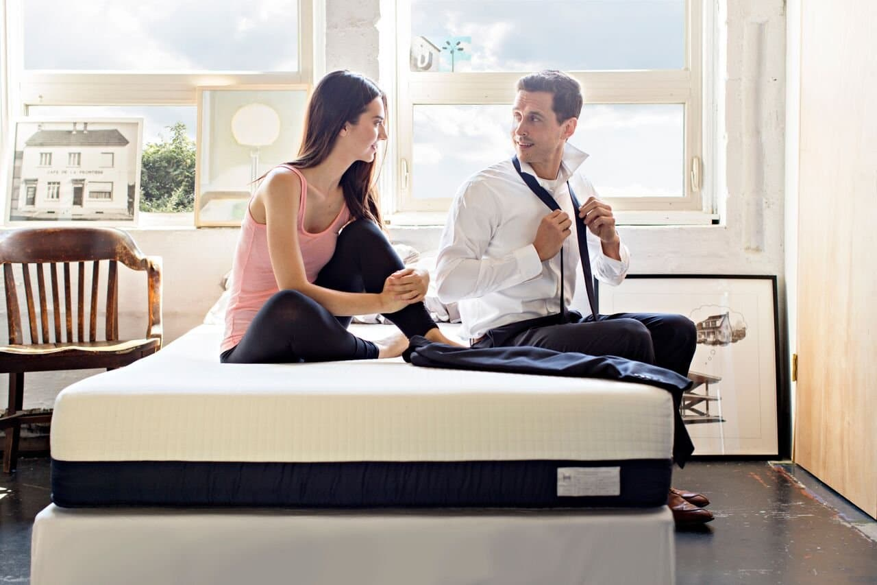 A man and woman sat on their Helix mattress