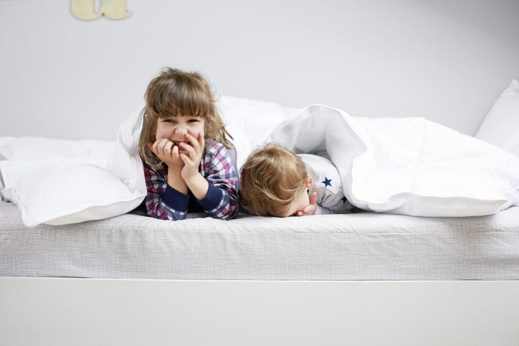Two children laying on a kids mattress