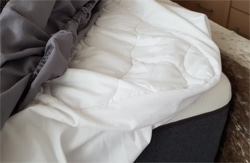 Crumpled sheets and mattress protector