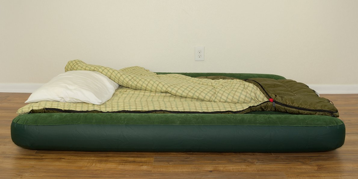 A fully made up air mattress with pillow and bedding