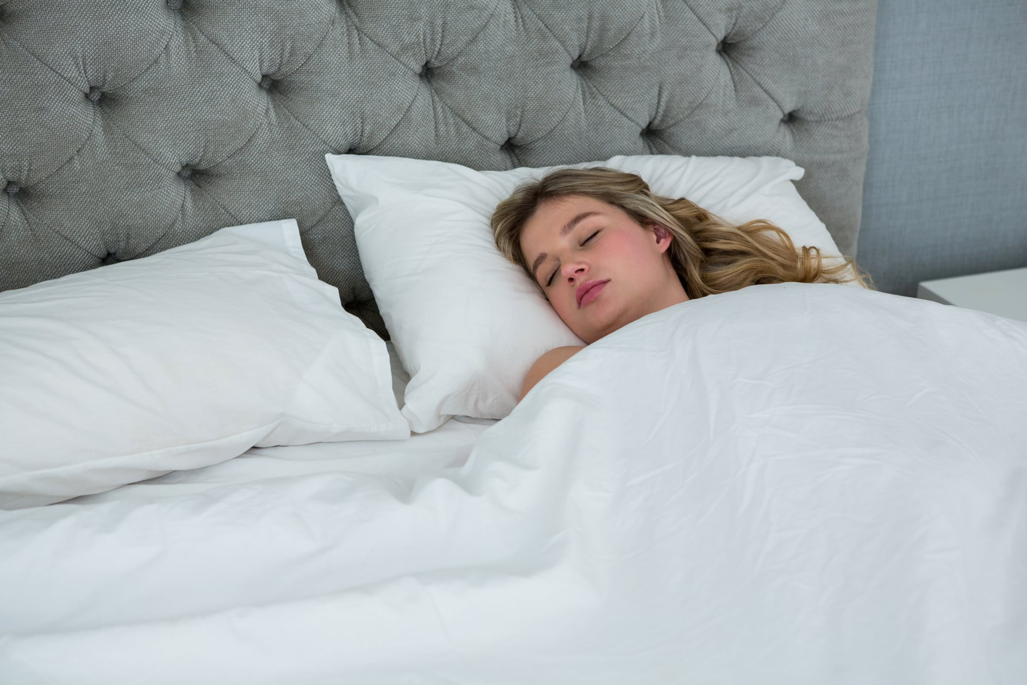 hot sleeping woman using a cooling blanket