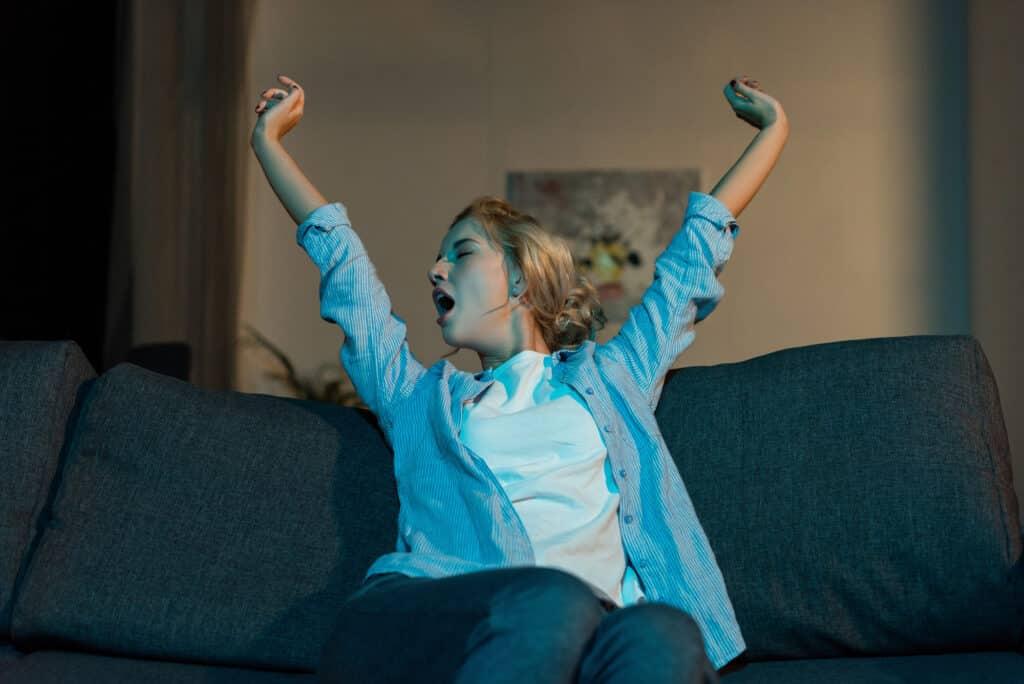 Yawning woman sitting on sofa