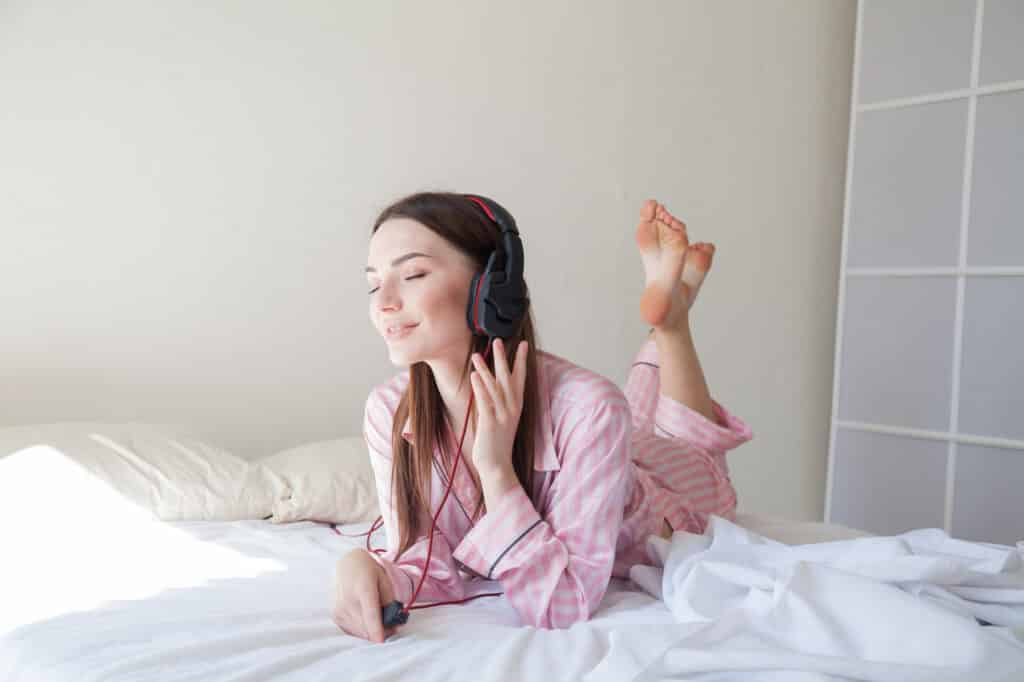 Young woman meditating and listening to music